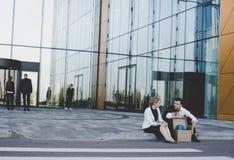 Hombre de negocios encendido que se sienta en la calle Fotos de archivo