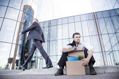 Hombre de negocios encendido que se sienta en la calle Fotos de archivo libres de regalías