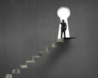 Hombre de negocios encima de las escaleras del dinero con el agujero de la cerradura fotografía de archivo libre de regalías