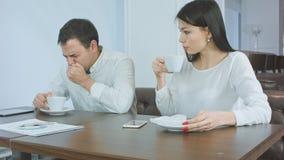Hombre de negocios enfermo que estornuda mientras que la hembra ansiosa que comprueba el suyo va a fiebre y el donante le de la s foto de archivo libre de regalías