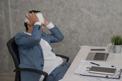 Hombre de negocios enfermo que toca su cabeza con las manos mientras que usa lapto fotos de archivo