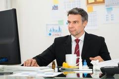Hombre de negocios enfermo usando el ordenador Foto de archivo libre de regalías