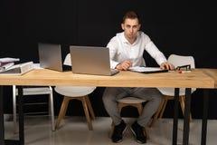 Hombre de negocios enfocado de los serios que piensa en tarea en línea imágenes de archivo libres de regalías