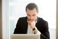 Hombre de negocios enfocado que busca la solución en Internet imagen de archivo
