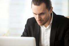 Hombre de negocios enfocado que mira en la pantalla del ordenador portátil imagen de archivo libre de regalías