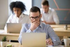 Hombre de negocios enfocado que soluciona el problema en línea que trabaja en el ordenador portátil adentro fotos de archivo libres de regalías