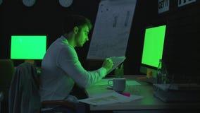 Hombre de negocios enfocado que trabaja con la pantalla verde delantera del documento en oficina de la noche metrajes
