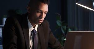Hombre de negocios enfocado que trabaja en el ordenador portátil en la noche