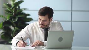 Hombre de negocios enfocado que trabaja mirando el ordenador portátil que hace notas en el lugar de trabajo metrajes