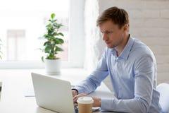 Hombre de negocios enfocado que usa el ordenador portátil, mirando la pantalla, haciendo compu fotografía de archivo libre de regalías