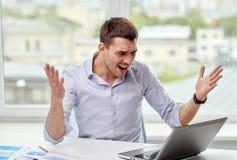Hombre de negocios enojado con el ordenador portátil y los papeles en oficina Foto de archivo libre de regalías