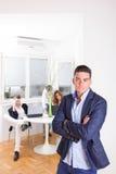 Hombre de negocios enojado delante de los colegas que trabajan como equipo Imagen de archivo libre de regalías