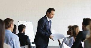 Hombre de negocios enojado no satisfecho con resultados del grupo de los empresarios después de seminario de entrenamiento durant almacen de video