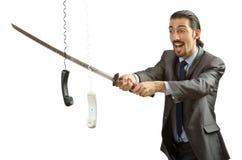 Hombre de negocios enojado que corta el cable Imagen de archivo