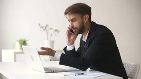 Hombre de negocios enojado que discute hablar de grito en el teléfono móvil que mira el ordenador portátil almacen de video