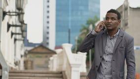 Hombre de negocios enojado que habla el teléfono móvil y que jura con su empleado al aire libre