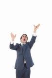 Hombre de negocios enojado que intenta alcanzar para algo desde arriba Foto de archivo libre de regalías