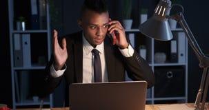 Hombre de negocios enojado que intenta solucionar problema de negocio en línea en la oficina de la noche