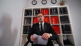 Hombre de negocios enojado que rasga para arriba un documento, un contrato o un acuerdo almacen de metraje de vídeo