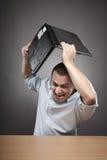 Hombre de negocios enojado que rompe su computadora portátil Imágenes de archivo libres de regalías
