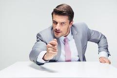Hombre de negocios enojado que se sienta en la tabla Imagen de archivo libre de regalías