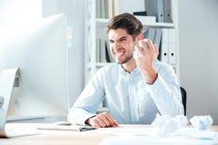 Hombre de negocios enojado que se sienta y documento de arrugamiento sobre su lugar de trabajo Foto de archivo