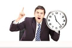 Hombre de negocios enojado que sostiene un reloj Imagen de archivo libre de regalías