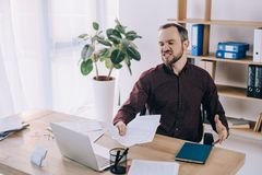 hombre de negocios enojado y con exceso de trabajo con los papeles en el lugar de trabajo con el ordenador portátil Fotografía de archivo