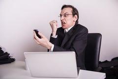 Hombre de negocios enojado y frustraded que grita en un teléfono celular en la oficina Imagen de archivo libre de regalías