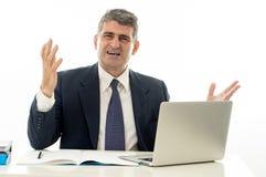 Hombre de negocios enojado y frustrado con el ordenador portátil que grita y que se preocupa foto de archivo