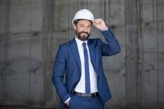 Hombre de negocios envejecido centro en el casco y el traje que se colocan y que sonríen en el trabajo Fotografía de archivo