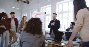 Hombre de negocios envejecido centro profesional del mentor que comparte experiencia con el equipo diverso en el seminario de mod almacen de video