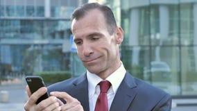 Hombre de negocios envejecido centro Using Smartphone para hojear en línea almacen de metraje de vídeo