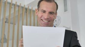Hombre de negocios envejecido medio Celebrating Success mientras que lee documentos en oficina metrajes
