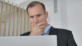 Hombre de negocios envejecido medio chocado Working en el ordenador portátil, asombroso metrajes