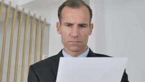 Hombre de negocios envejecido medio pensativo Reading Documents en la oficina, papeleo almacen de metraje de vídeo