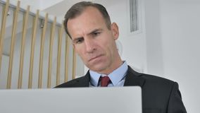 Hombre de negocios envejecido medio pensativo Thinking y trabajo en el ordenador portátil almacen de video