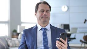 Hombre de negocios envejecido medio que reacciona a la pérdida mientras que usa smartphone almacen de video
