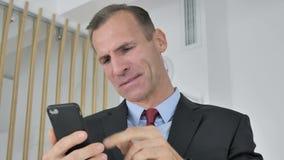 Hombre de negocios envejecido medio Reacting del trastorno tenso a la pérdida en Smartphone metrajes