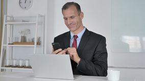 Hombre de negocios envejecido medio Using Smartphone para el comercio financiero en línea metrajes