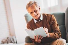 Hombre de negocios envejecido que comprueba a su planificador semanal foto de archivo