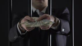 Hombre de negocios esposado que sostiene los billetes de banco del dólar, evasión fiscal, blanqueo de dinero metrajes