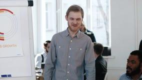 Hombre de negocios europeo sonriente acertado joven que habla en el seminario de moda de la oficina, explicando datos de las fina almacen de video