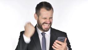 Hombre de negocios Excited de la barba para el éxito mientras que usa Smartphone metrajes