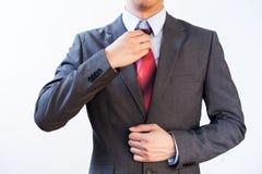 Hombre de negocios Executive que ajusta el lazo rojo aislado en el fondo blanco Fotos de archivo libres de regalías