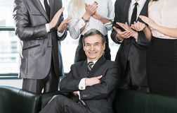 Hombre de negocios experimentado a la edad del aplauso en el fondo de sus empleados imagen de archivo libre de regalías