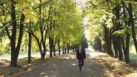 Hombre de negocios feliz acertado en el baile del traje en el parque del otoño que disfruta de éxito almacen de video