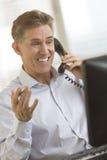 Hombre de negocios feliz Communicating On Telephone mientras que mira el Co Foto de archivo libre de regalías