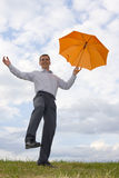 Hombre de negocios feliz con el paraguas anaranjado Foto de archivo libre de regalías
