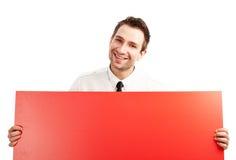Hombre de negocios feliz con la cartelera roja en blanco Fotografía de archivo